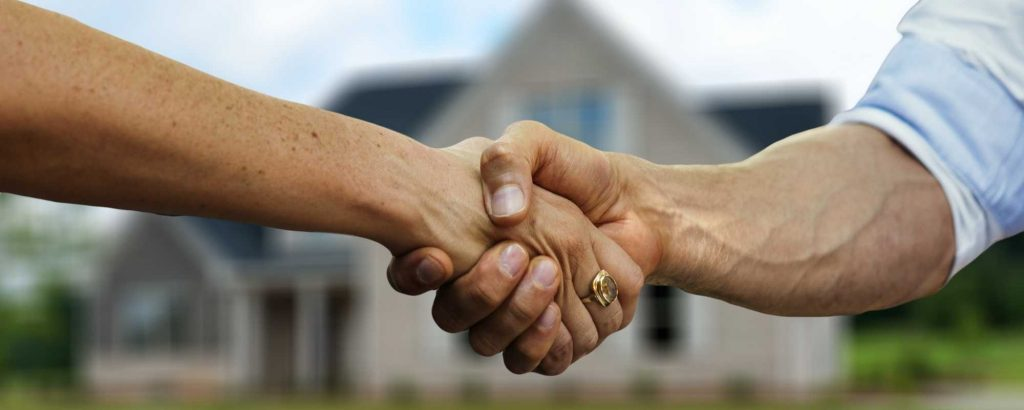 Two men shake hands in front of a home.