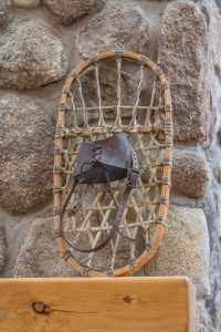 Beautiful natural stone fireplace with rustic snowshoe decor