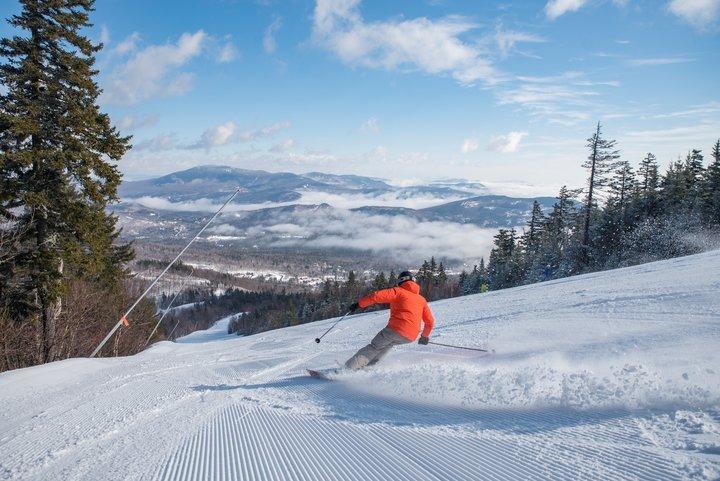 Skier in orange jacket on groomed trail