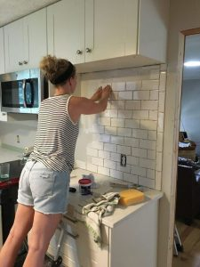 woman installing subway backsplash tile