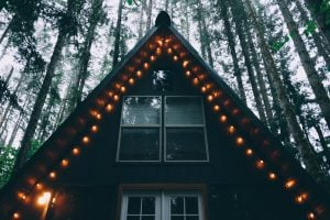 A-frame ski home in the woods with lights on the roof